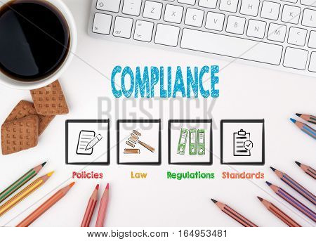 Compliance, Business concept. White office desk Computer keyboard, coffee mug and colored pencils