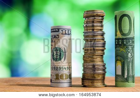 One hundred euro and one hundred US dollar rolled bills banknotes with euro coins and american cents on green blurred bokeh background.