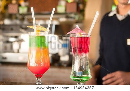 Colored cocktails on a background of bar Colorful cocktails near the bar. . Summer drinks. Exotic drinks. Glasses of cocktails on table near pool. Summer drinks photo concept. Сocktail