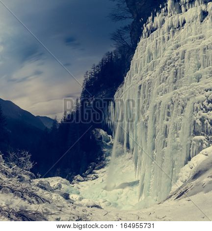 Frozen waterfall at night. Icicles hanging from sheer wall of Pericnik Slap, Vrata in Slovenia.