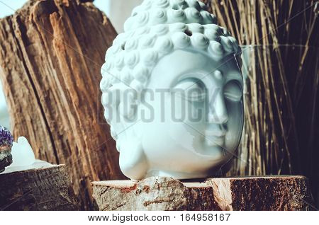 White head of Buddha with purple amethyst stone on wooden background. Buddhism religion concept. Esoteric yoga meditation spiritual enlightenment.