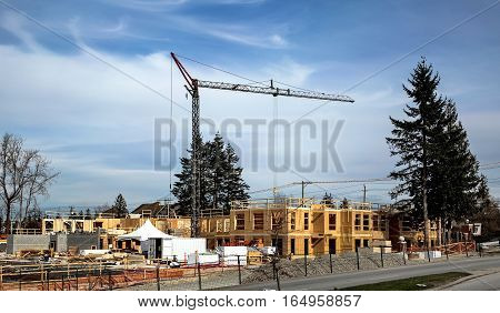Construction site under construction new wooden apartment house, already raised two floors, construction crane, construction machinery, building materials, working platform.