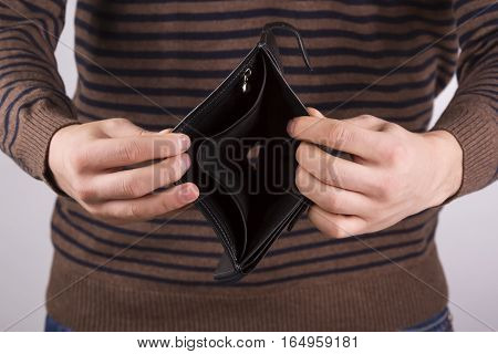 man holding an empty wallet on a light background