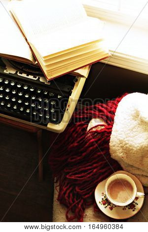 Cozy sunlit morning still life by windowsill. Vintage typewriter with open book, warm blanket and chair accompanied by beautiful antique teacup and saucer.
