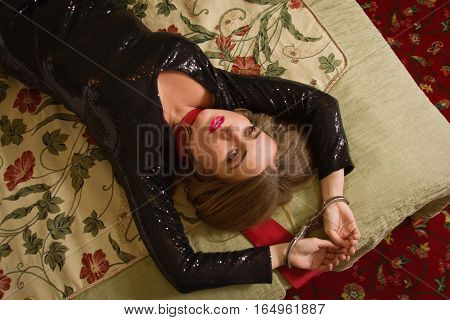 Strangled Beautiful Woman In A Black Dress Lies On A Bed. Simulation Of The Crime Scene.