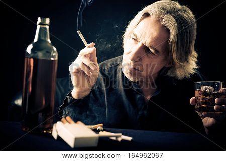 Studio shot of senior man with whiskey bottle.