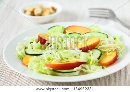 Fresh nectarine cucumber and iceberg lettuce salad on plate photographed with natural light (Selective Focus Focus in the middle of the salad)