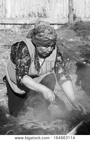 ACHAO CHILE - FEBRUARY 6 2016: Unidentified woman uncovering the traditional Chilotan dish Curanto al hoyo at the Muestras Gastronomicas 2016 (Gastronomy Show) in Achao Chiloe Archipelago Chile (Digitally Altered: Monochrome Image)