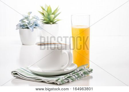 Cup of hot coffee and glass of orange juice with potted plants in background.