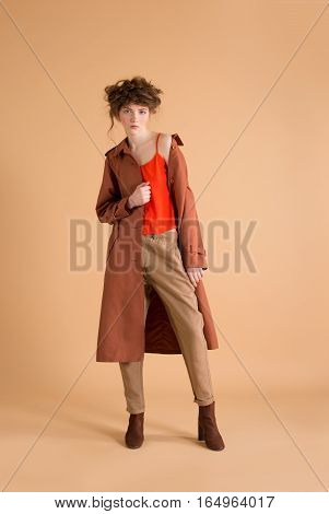 redhead woman with freckles wearing beige pants orange shirt and pants korichnivoe coat on a beige background. Fashion photo concept