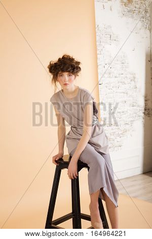 Redhead with freckles wearing a blue skirt and blouse on a beige background. A woman sits on a chair. Fashion model. Woman with perfect skin. Woman wi with nude makeup. Fashion photography concept