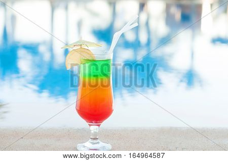 Colored cocktails on a background of water. Colorful cocktails near the pool. Beach party. Summer drinks. Exotic drinks. Glasses of cocktails on table near pool. Summer drinks photo concept. Сocktail