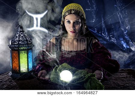 Psychic or fortune teller with crystal ball and horoscope zodiac sign of Gemini