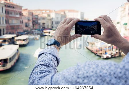 male tourist to venice taking pictures with his phone