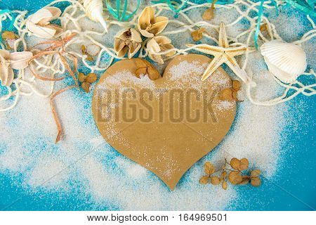brown paper heart in sand with seashell and starfish in net