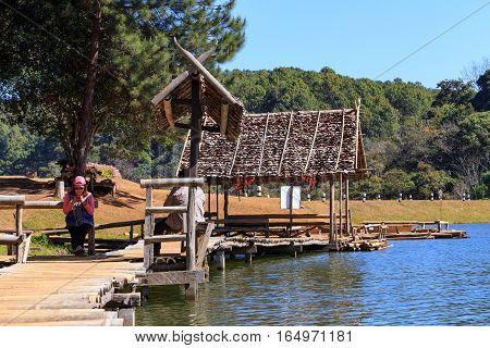 Traveler Relaxing On Bamboo Bridge And Hut In Lake