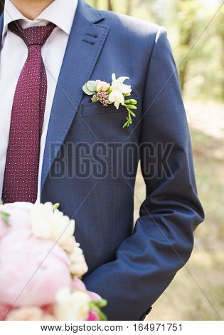 Boutonniere groom in a blue suit.  Wedding photo concept