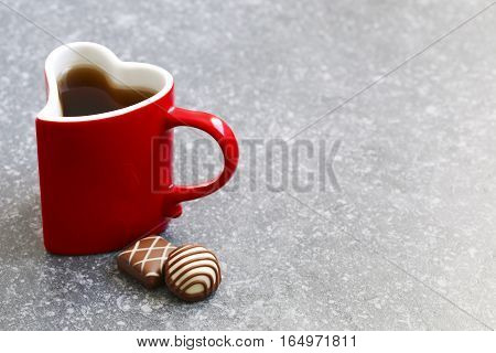 Heart shaped cup of tea and chocolate candy. Valentines day concept. Top view