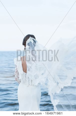The bride in a beautiful dress and vintage faie looking at the sea. Dress with open back. veil flies. Wedding dress with lace. Wedding photo concept. Bride. Art wedding photo