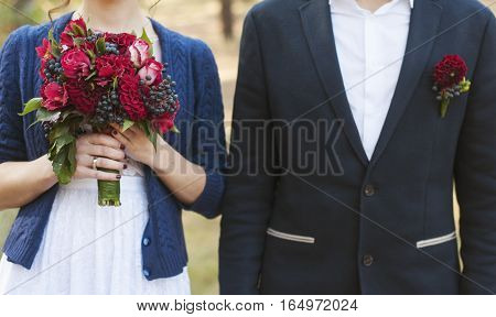 Bride and groom in a forest. Sensual photo of the groom and bride Wedding photo concept. Bridal bouquet and boutonniere. Wedding photo concept. Autumn wedding
