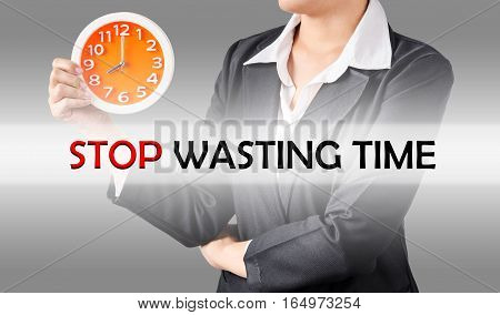 Stop wasting time and business woman holding clock. Business concept.