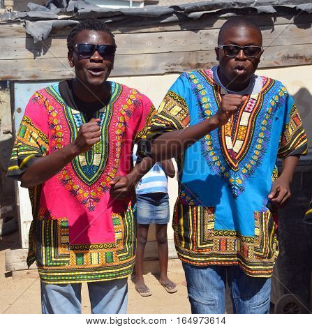 SWAKOPMUND, NAMIBIA OCTOBER 09, 2014: Unidentified young men street singers in Mondesa slum of Swakopmund on october 09 2014. In Namibia About 27.6 per cent of households are classified as poor.