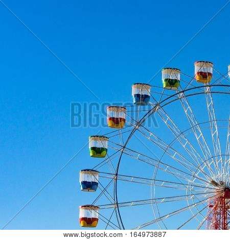 Colorful ferries wheel against blue sky on the background