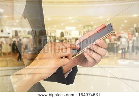 Young Business woman using mobile smart phone on blurred shopping mall background. Shopping online concept.