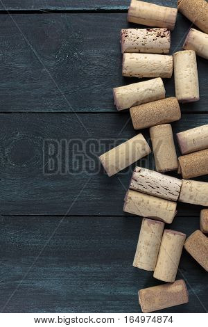Many wine corks on a dark wooden background texture with copyspace. A horizontal design template for a tasting invitation or restaurant menu