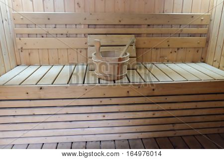 Bucket for water and pillows on bench in Finnish sauna.