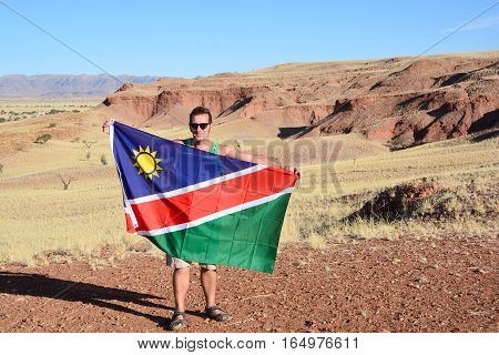 Namib-Naukluft Park in Namibia 10 10 2014: Man waving the flag of Namibia in Namib-Naukluft National Park is a national park of Namibia encompassing part of the Namib Desert world's oldest desert