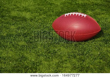 An American football resting on artificial turf field.