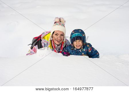 Cheerful mother and son in snow having fun together