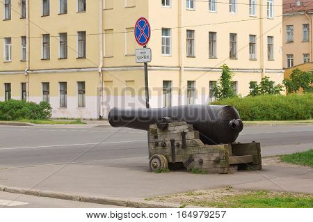 Urban exterior with antique cannon at the crossroads. Urban architecture