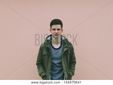 Young man in jacket on the pink wall background