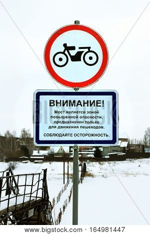Prohibiting road sign - the Movement of motorcycles is prohibited. Sign installed at a pedestrian pontoon bridge across the river