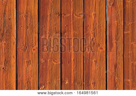 Closeup on a red wooden wall in bright sunshine. Planks, boards red painted.