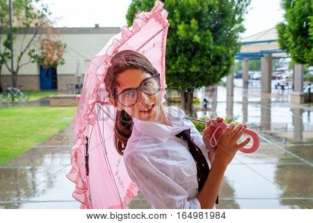 A girl wearing a clip on tie and large glasses stands under a frilly pink umbrella in the rain. She is leaning slightly backwards.