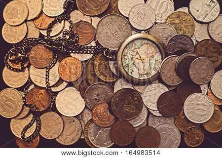 Time is money, a bunch of coins with a pocket watch on top