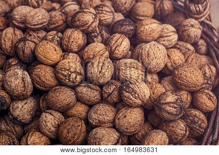 Walnuts in wicker basket, closeup top view