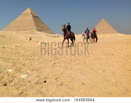 Two tourists and guide riding horses past the Great Pyramids of Egypt in January 2014.
