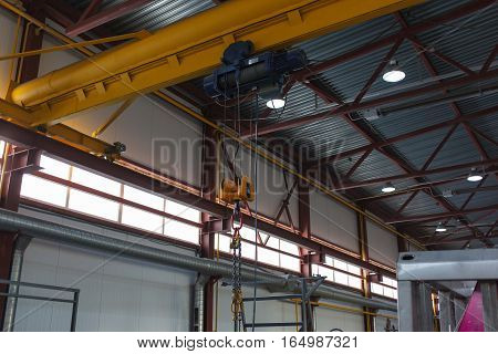 Five-ton yellow crane in the factory. Close-up.
