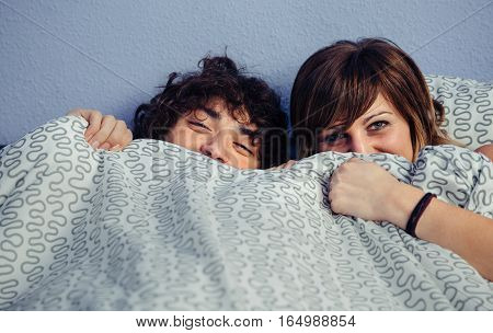 Closeup of happy young couple in love laughing and covering their mouths under a duvet. Love and couple relationships concept.