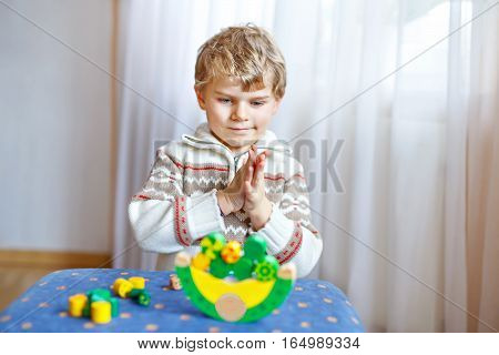 Cute blond child playing with lots of colorful wooden blocks indoor. Active funny kid boy having fun with building and creating, balance toy. Kindergarten. Home, kidsroom. Cognitive development
