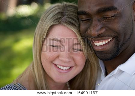Loving multicultural couple hugging and smiling outside.