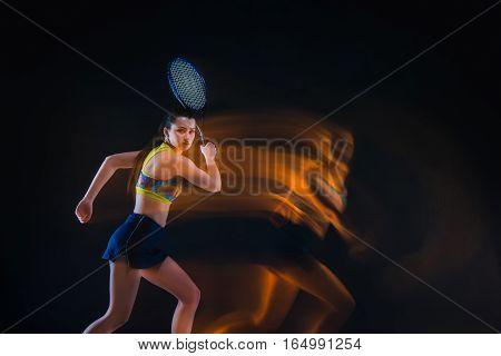 Portrait of beautiful girl tennis player with a racket on dark studio background. Stroboscope shooting technique