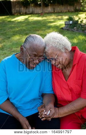 Mature African American best friends laughing and smiling.