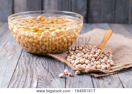 Uncooked chickpeas in wooden spoon on wooden background