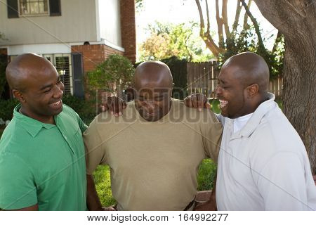 Happy African American father and his adult sons.