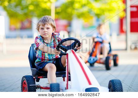 Two active little kid boys driving pedal race car in summer garden, outdoors. Children, best friends racing with fast speed and having fun. Twins making competition